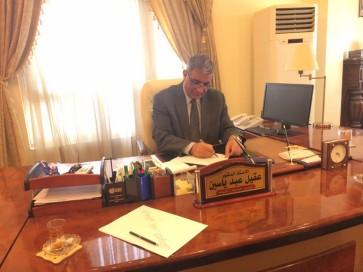 الدكتور عقيل عبد ياسين رئيس جامعة الكوفة و هو يكتب رسالة الى الموصل