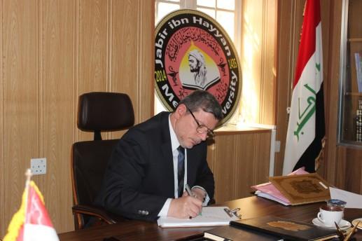 الدكتور علي الصائغ رئيس جامعة ابن حيان الطبية و هو يكتب رسالته الى الموصل